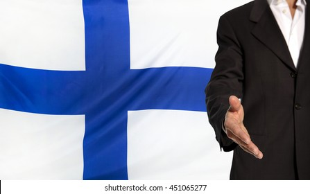 Businessman with an open hand waiting for a handshake concept for business with the Finland flag in the background