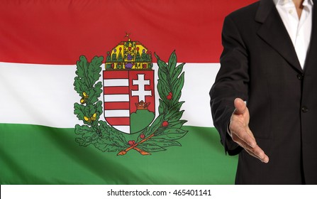 Businessman with an open hand waiting for a handshake concept for business with the Hungary Coat of Arms flag in the background
