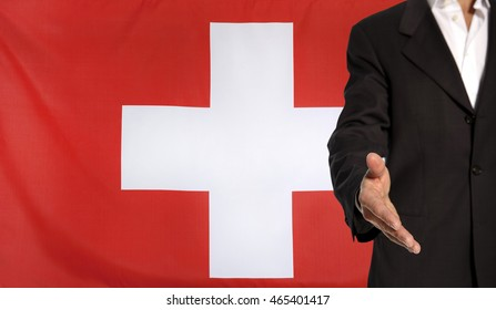 Businessman with an open hand waiting for a handshake concept for business with the Switzerland flag in the background