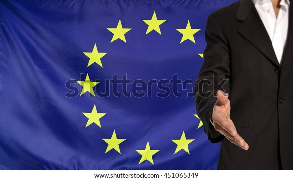 Businessman with an open hand waiting for a handshake concept for business with the Europe flag in the background