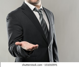 Businessman with open palm offering something. Close-up of young businessman's hand in concept of holding or giving.