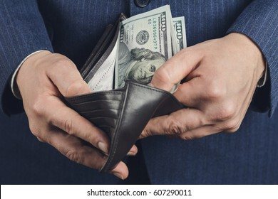 Businessman opened the wallet with hundred dollar banknotes, close-up view, business and finance concept