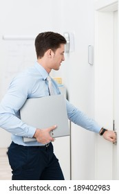 Businessman opening a door as he leaves the office with a binder under his arm