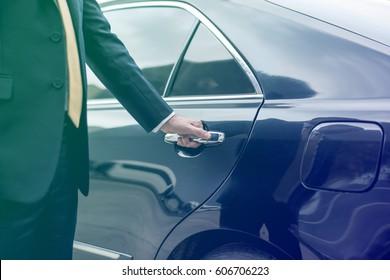 Businessman opening limo car door