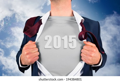 Businessman opening shirt in superhero style against blue cloudy sky