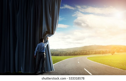 Businessman opening velvet curtain to countryside road