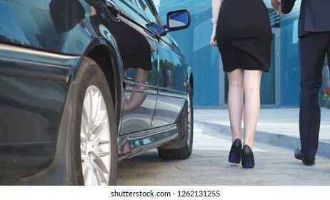 Businessman opens door for beautiful young woman. Man uncover door of automobile for female passenger. Girl get out from auto and leaves with her boyfriend to modern office building. Slow motion.