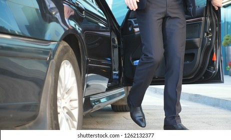 Businessman opens door and get out from the car near modern office building. Young business man uncover door of automobile. Guy in suit exit from black auto. Commuter to job. Slow motion Close up.