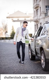 Businessman opens the door of his car standing on the roadway