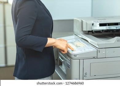 A businessman operating a copy machine