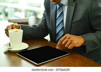 Businessman operating his digital tablet at cafe