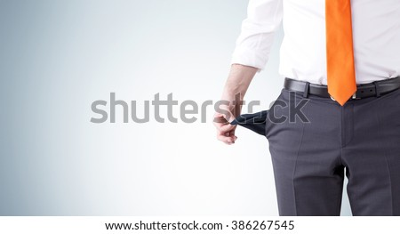 A businessman with an orange tie turning his empty pockets inside out. Front view, no head. Grey background. Concept of bankruptcy.