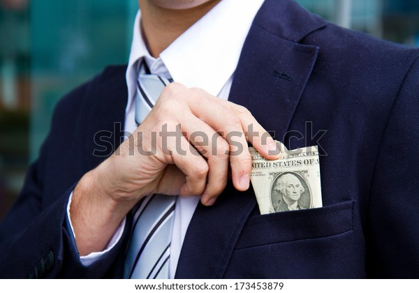 businessman outside office taking banknotes
