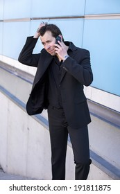 businessman outside on the phone and looking very concerned