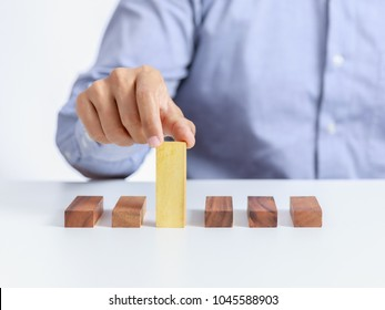 businessman and outstanding wooden toy block, different concept
