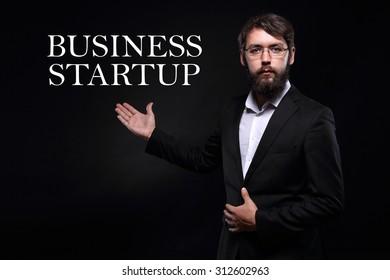 "Businessman over black background presenting ""Business startup"""