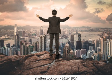 businessman over hill far to the city with open arms