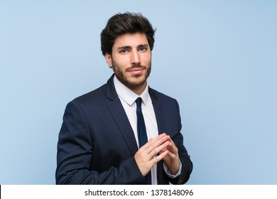 Businessman over isolated blue wall scheming something