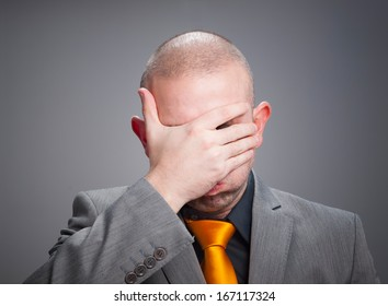 Businessman overwhelmed with hand on his face and isolated on dark background.