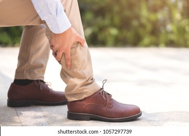 Businessman pain his feet and legs after walked a lot for his work