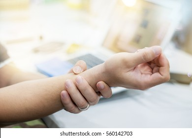 Businessman with pain on the wrist at office