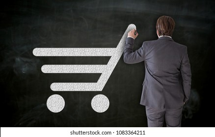 Businessman paints shopping cart on blackboard Concept.