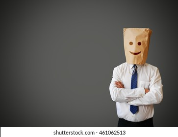 Businessman with a paper bag with funny face on the head
