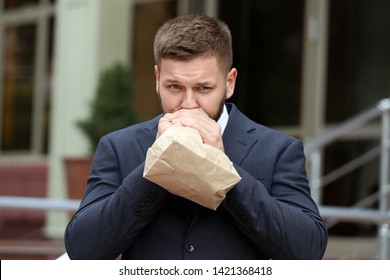 Businessman with paper bag having panic attack outdoors