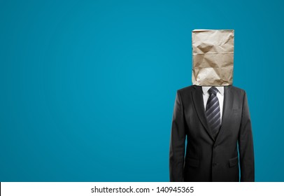 businessman with paper bag on head isolated on blue