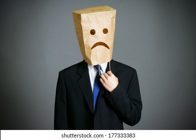 Businessman with a paper bag with sad face on the head