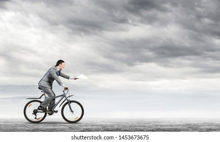 Businessman with paper documents in hand on bike. Deadline for paperwork. Corporate employee in grey business suit riding bicycle on background of skyscape. Accounting and financial statements