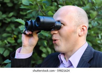 Businessman in the park looking through binoculars