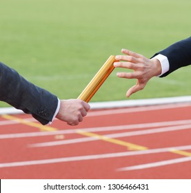 Businessman passing baton in relay race