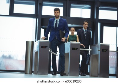 Businessman passing through turnstile gate at office