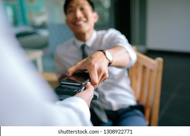 Businessman paying bill through smartphone using NFC technology in restaurant. Closeup of male hand holding his mobile phone over a card reader machine for doing the payment.