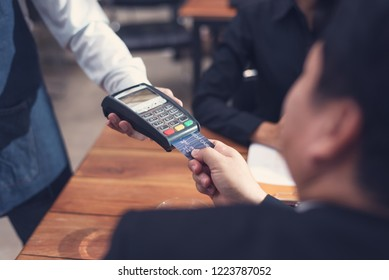 Businessman paying by credit card with a credit card reader machine in a restaurant