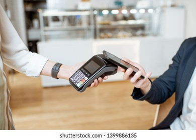 Businessman paying contactless with smart phone while sitting at the cafe, close-up view