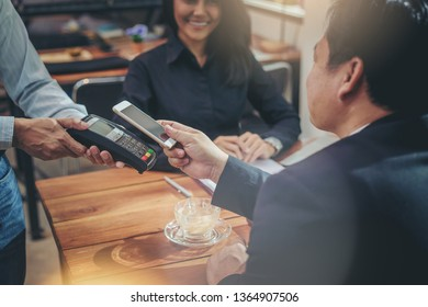 Businessman paying with NFC technology by smartphone in coffee shop. mobile QR code payment concept