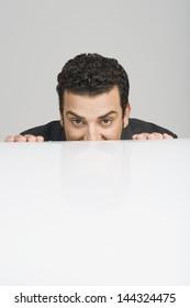 Businessman peeking over a desk