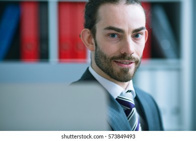 Businessman peeping from behind the monitor, looking into the camera