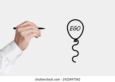 Businessman with a pen is about to pop a balloon icon with the word ego. Lower or free your ego concept.