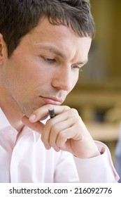 Businessman with pen, hand to face, close-up