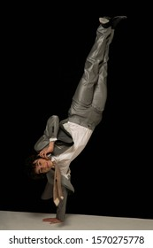 A businessman performs a one armed handstand, talking on the phone