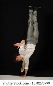 A businessman performs a one armed handstand, waving his hand