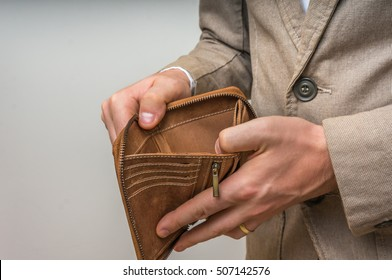 Businessman person holding an empty wallet, he has no money
