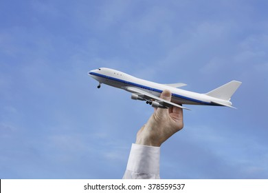 Businessman or Person Holding Model Airplane in a Blue Sky