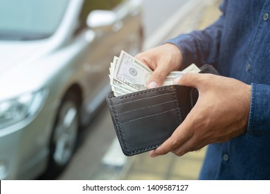 Businessman Person holding a wallet in the hands of take money out of pocket stand front car prepare pay by installments - insurance, loan and buying car finance concept insurance, payment a car - Shutterstock ID 1409587127