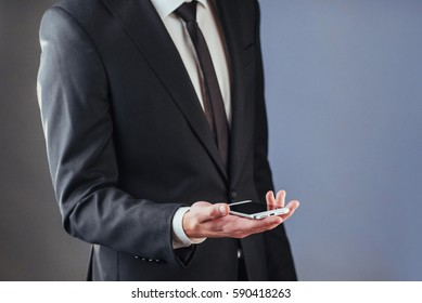 Businessman with a phone in his hand. A student in a suit on a dark background
