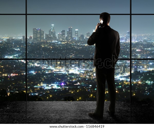 businessman with phone looks in night city
