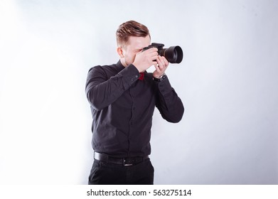 Businessman photographed in the studio. Photographer man in a black shirt and pants standing with camera.